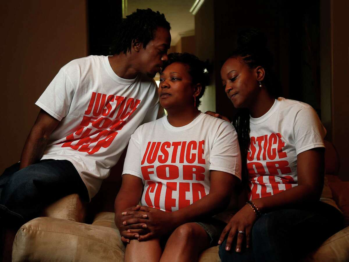 """Margaret Pink-Green, flanked by her son Ellis and daughter Erika Pink, says she would like """"some closure"""" in the homicide of her eldest child, Eric, whose nickname was """"Sleepy."""" They're wearing T-shirts emblazoned with """"Justice for Sleep"""" in his honor."""