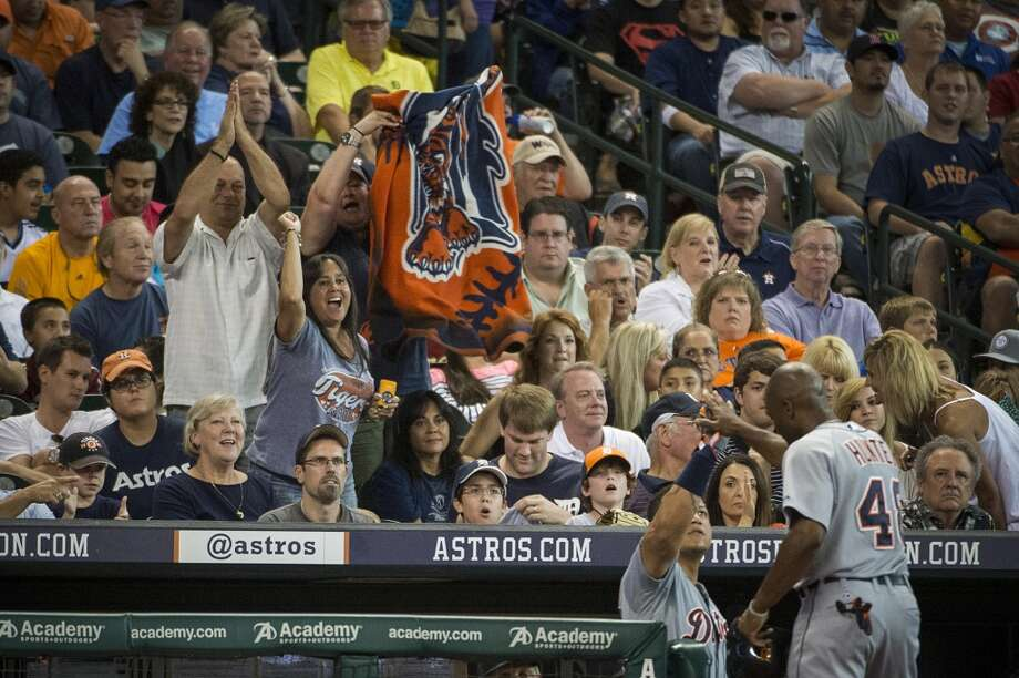 A group of Detroit Tigers fans cheer as Miguel Cabrera congratulates Torii Hunter (48) after he scored during the fifth inning. Photo: Smiley N. Pool, Houston Chronicle