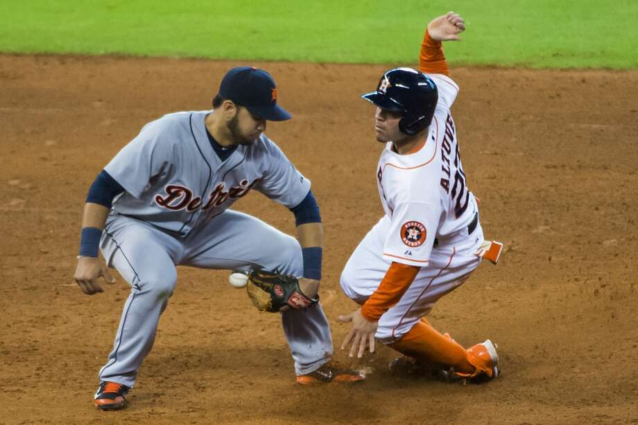 Jose Altuve is safe at second base with his 34th stolen base of the season as the ball gets away from Detroit Tigers shortstop Eugenio Suarez. Photo: Smiley N. Pool, Houston Chronicle