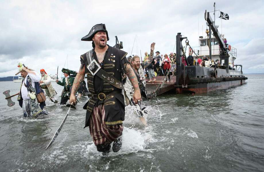 Seafair Pirates disembark from their landing craft as they arrive at Alki Beach on Saturday, June 28, 2014. The landing of the pirates brought out thousands of people that lined the shore to watch the event. To many, the Seafair Pirates landing is an unofficial kickoff of summer. Photo: JOSHUA TRUJILLO, SEATTLEPI.COM / SEATTLEPI.COM