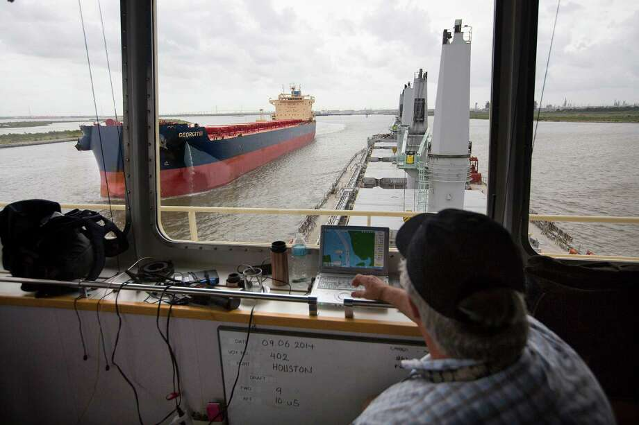 A Houston Ship Channel pilot leads the Ocean Lark, a 620-by-106-foot ship on its way to Brazil, past the Georgitsi. Harris County's narrow channel is one of the busiest in the world. Photo: Johnny Hanson / © 2014  Houston Chronicle