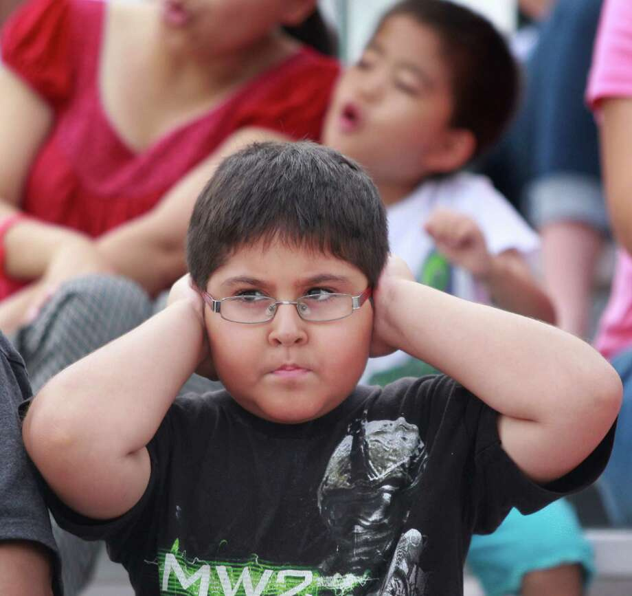 Fabian Arellano, 6, of Houston covers his ears while watching the IndyCar Series Race #1 at the Grand Prix of Houston at NRG Park Saturday, June 28, 2014, in Houston. Photo: Melissa Phillip, Houston Chronicle / © 2014  Houston Chronicle