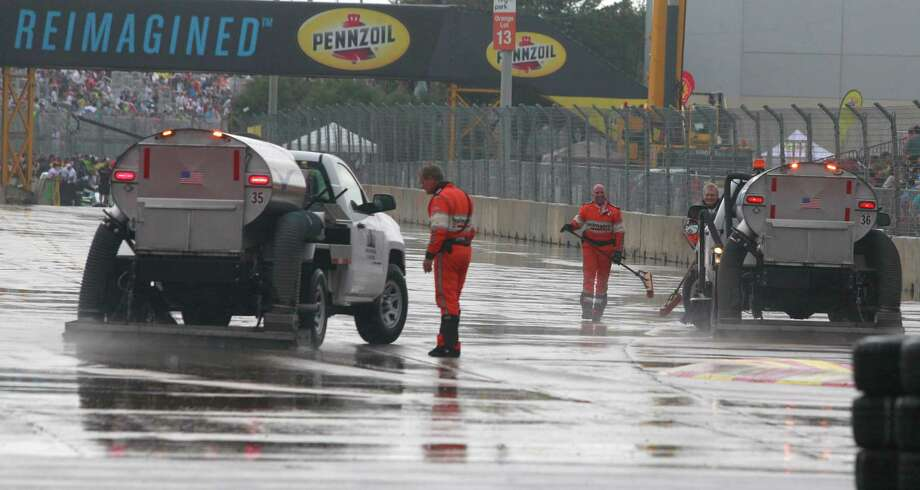 Crews work to move rain water off the track before the start of the IndyCar Series Race #1 at the Grand Prix of Houston at NRG Park Saturday, June 28, 2014, in Houston. Photo: Melissa Phillip, Houston Chronicle / © 2014  Houston Chronicle