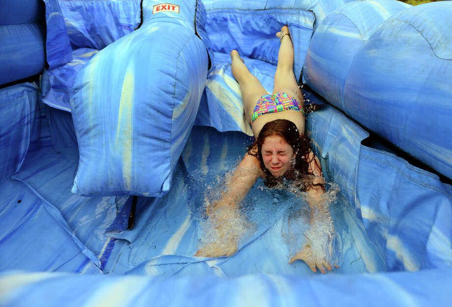 Morgan Albert, 14, lands in the pool at the bottom of an inflatable waterslide, during a summer party at her friend's house in Shelton, Conn. on Saturday June 28, 2014. The slide is rented out to the the Rodriguez family by local business Huntington Rental. Photo: Christian Abraham / Connecticut Post