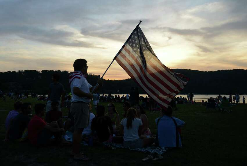 Justin Chan, of Danbury, waves an American Flag before the Independence Day fireworks display at Candlewood Town Park on Candlewood Lake in Danbury, Conn. Saturday, June 28, 2014.