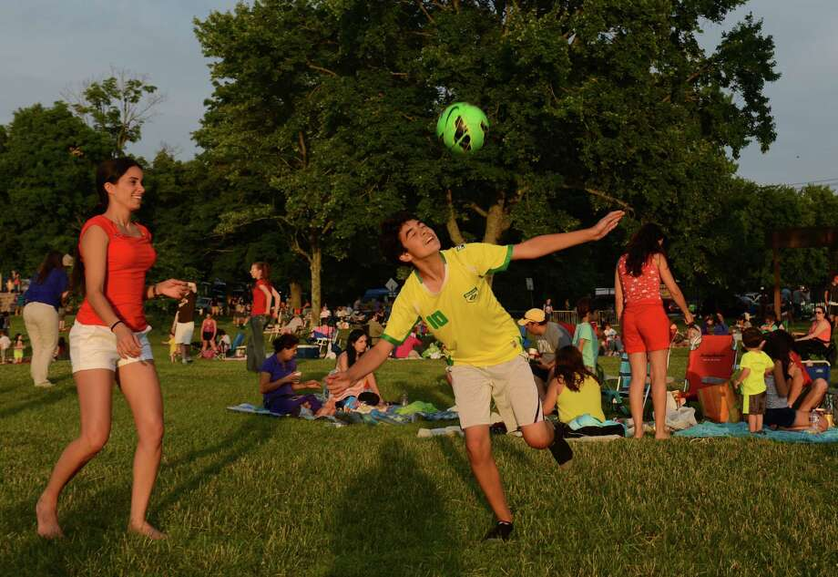 Danbury residents Marcia Haddad and Wallace Oliveira, 13, play soccer before the Independence Day fireworks display at Candlewood Town Park on Candlewood Lake in Danbury, Conn. Saturday, June 28, 2014. Photo: Tyler Sizemore / The News-Times