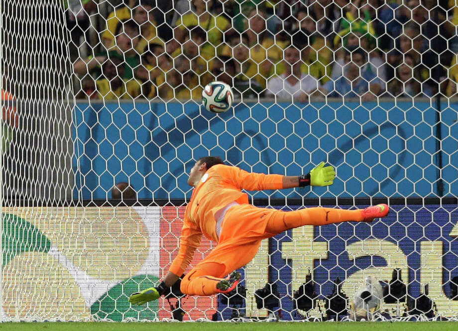 Uruguay keeper Fernando Muslera is powerless to stop a goal by Colombia's James Rodriguez, who leads the tournament with five goals in four games. Photo: Matt Dunham, STF / AP