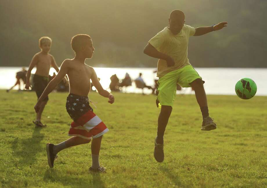 Children play soccer as the sun sets before the Independence Day fireworks display at Candlewood Town Park on Candlewood Lake in Danbury, Conn. Saturday, June 28, 2014. Photo: Tyler Sizemore / The News-Times