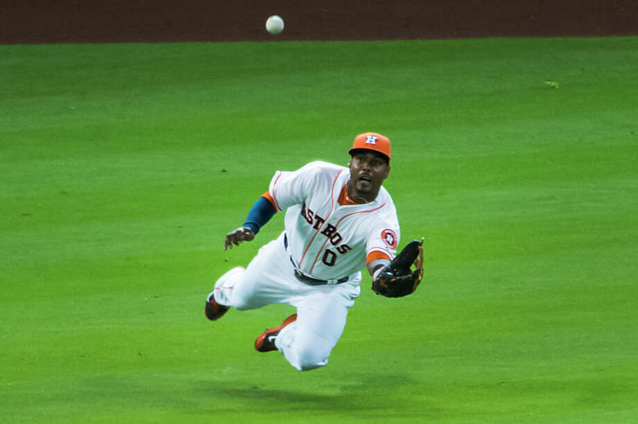 Astros left fielder L.J. Hoes makes a diving catch on a line drive by the Tigers' Ian Kinsler to end a bases-loaded threat in the seventh inning Saturday. Photo: Smiley N. Pool / © 2014  Smiley N. Pool