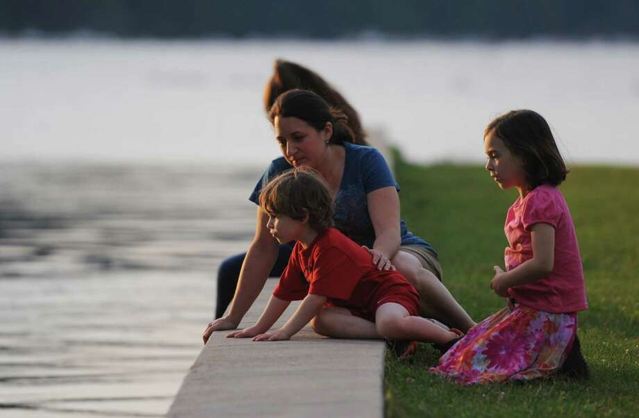 Michele Jonas, of Brookfield, looks into the water with her children Sam, 4, and Talia, 6, before the Independence Day fireworks display at Candlewood Town Park on Candlewood Lake in Danbury, Conn. Saturday, June 28, 2014. Photo: Tyler Sizemore / The News-Times
