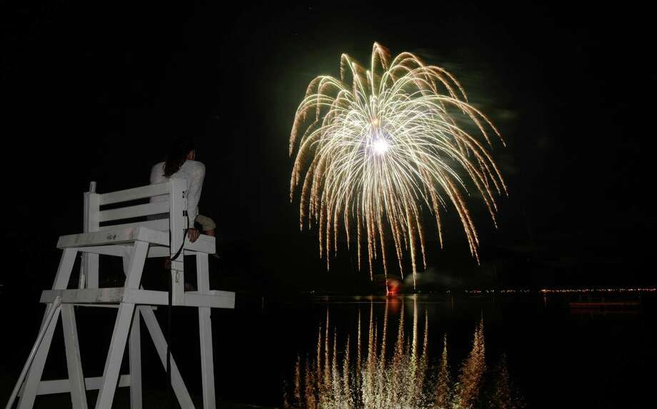 Andrea LaRosa, of Danbury, watches the Independence Day fireworks display from atop the lifeguard's chair at Candlewood Town Park on Candlewood Lake in Danbury, Conn. Saturday, June 28, 2014. Photo: Tyler Sizemore / The News-Times