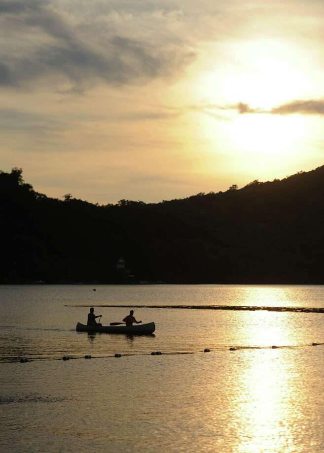 People paddle a canoe on Candlewood Lake before the Independence Day fireworks display at Candlewood Town Park in Danbury, Conn. Saturday, June 28, 2014. Photo: Tyler Sizemore / The News-Times