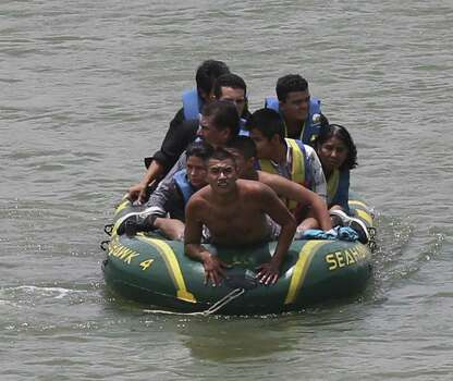 Using an inflatable raft, smugglers, carry immigrants across the Rio Grande near the international bridge in Roma. Law officials say higher-risk smuggling operations are moving into Starr County to avoid areas now saturated with officers. Photo: Jerry Lara / San Antonio Express-News / ©2014 San Antonio Express-News
