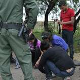 Immigrants remove their shoelaces as U.S. Border Patrol agents processed them in the Texas community of Granjeno.