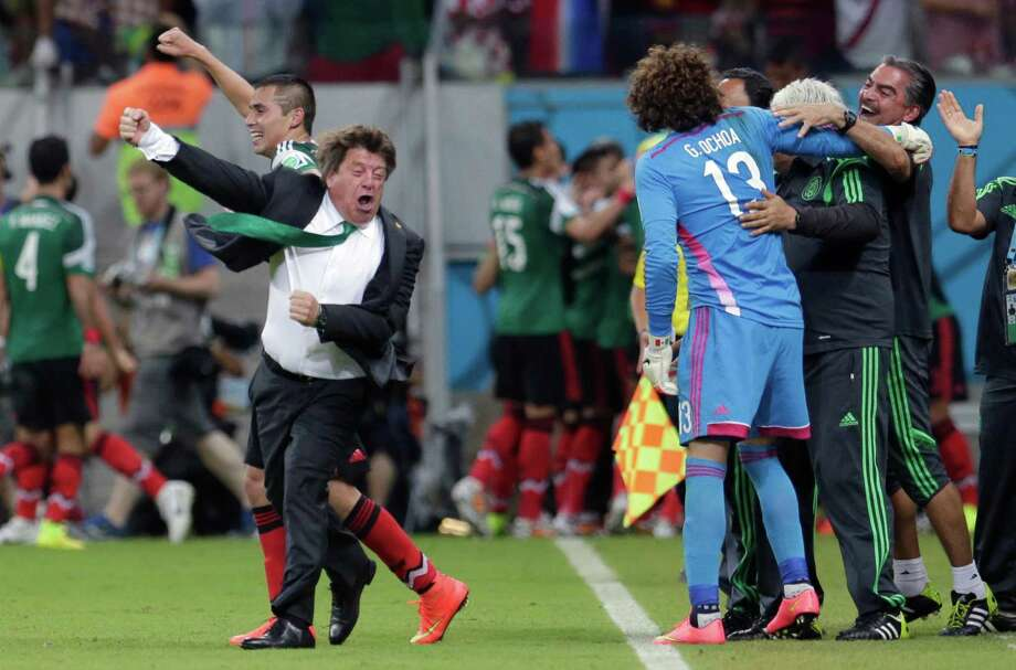 Mexico head coach Miguel Herrera, left, has been known for his sideline celebrations during World Cup matches this month. Photo: Petr David Josek, STF / AP