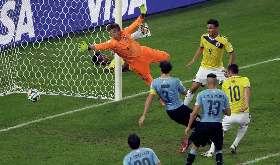 Colombia's James Rodriguez, right, scores his side's second goal past Uruguay's goalkeeper Fernando Muslera during the World Cup round of 16 soccer match between Colombia and Uruguay at the Maracana Stadium in Rio de Janeiro, Brazil, Saturday, June 28, 2014. (AP Photo/Themba Hadebe) Photo: Themba Hadebe, Associated Press / AP