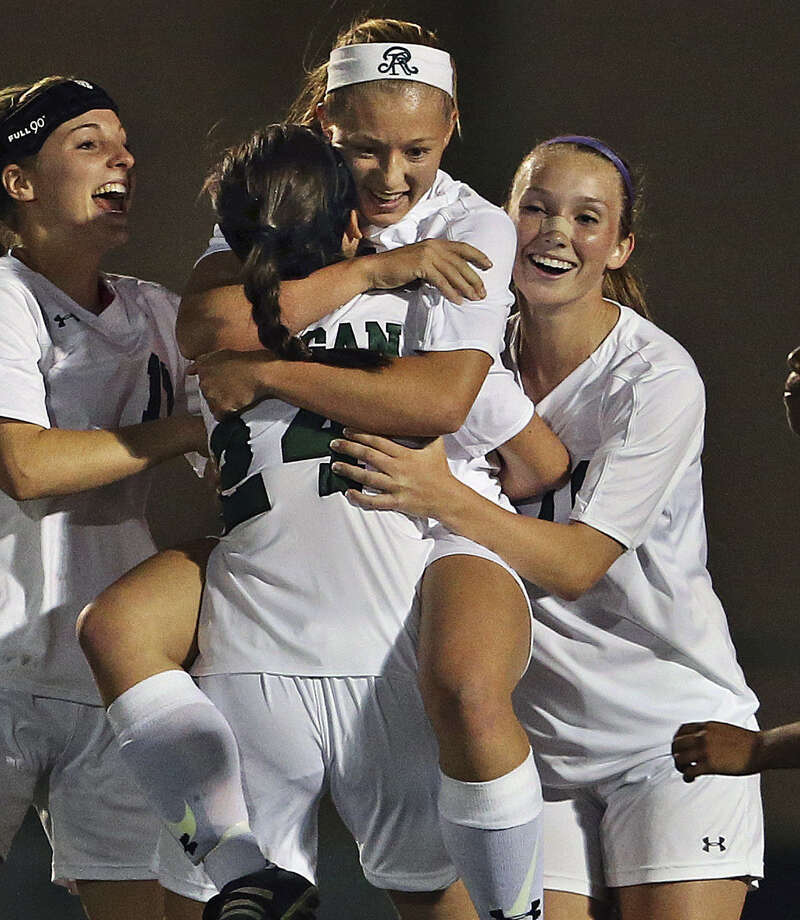 Reagan soccer player Taylor Olson is embraced by teammates after scoring in the Class 5A region quarters. Photo: Tom Reel / San Antonio Express-News / San Antonio Express-News