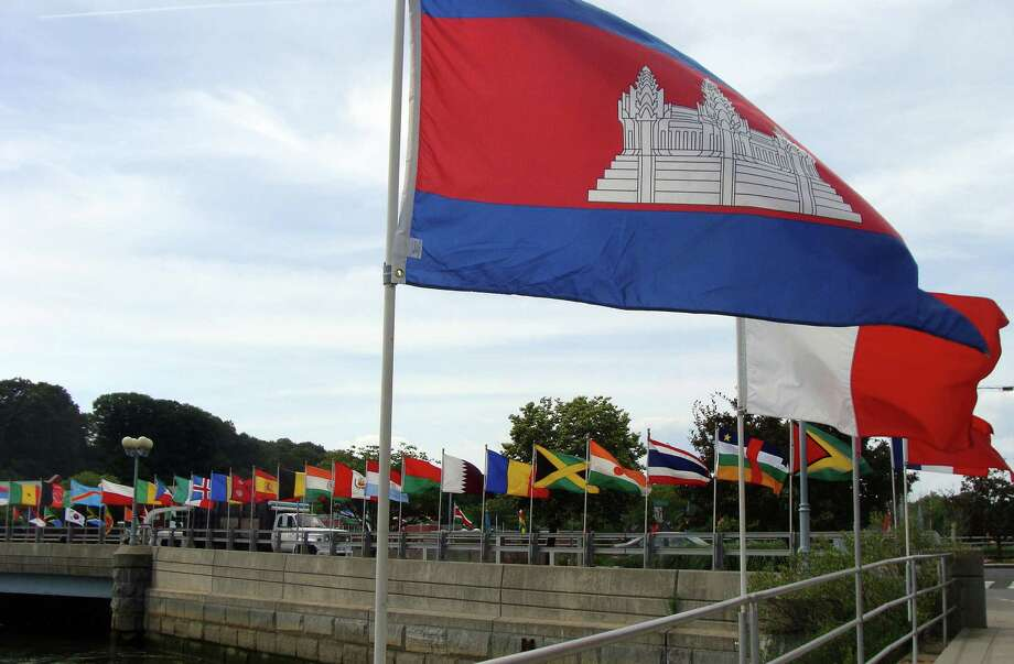 A colorful display of flags from many nations unfurled in strong breezes Saturday along the Post Road bridge as the town hosted United Nations visitors for the 49th annual jUNe Day. Photo: Meg Barone / Westport News