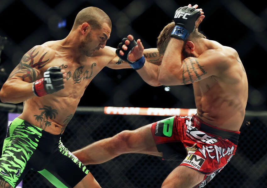 Jeremy Stephens folds under the attack of Cub Swanson in the main event during the UFC Fight Night at the AT&T Center on June 28, 2014.