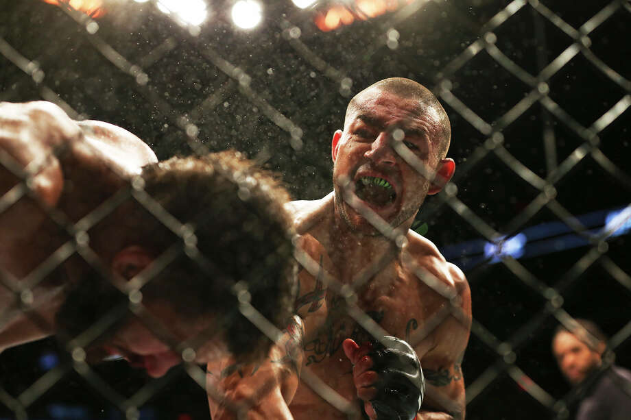 Cub Swanson attacks Jeremy Stephens on the wire during UFC Fight Night at the AT&T Center on June 28, 2014. Photo: TOM REEL, Tom Reel/Express-News