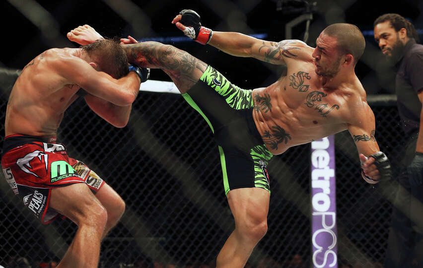 Jeremy Stephens (left)  is hit by a kick from  Cub Swanson  in the main event during the UFC Fight N