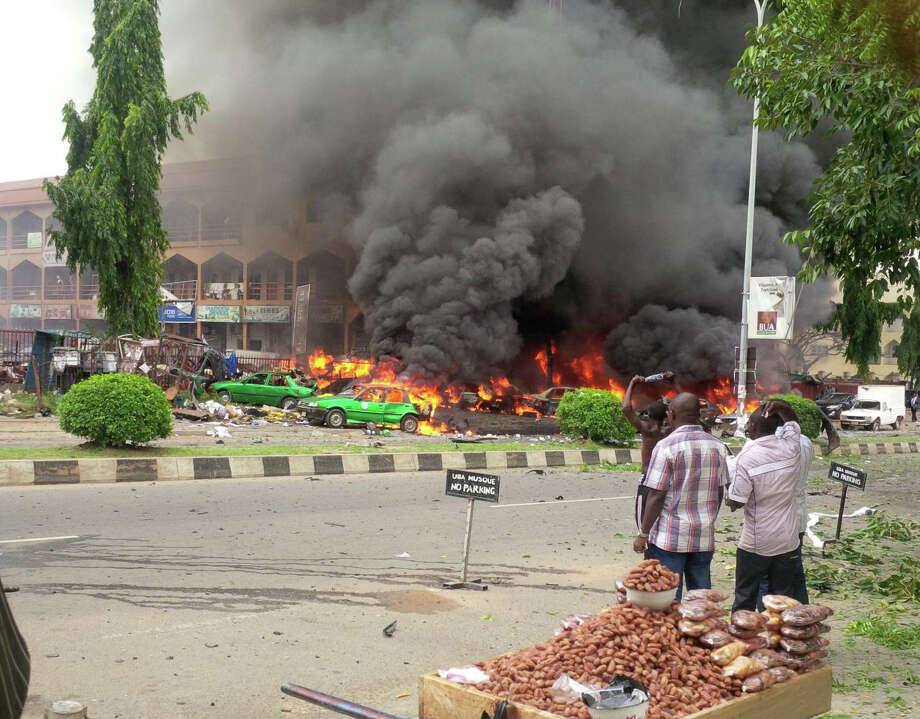 People watch as smoke fills the sky, after an explosion, at a shopping mall,  Wednesday, June 25, 2014, in Abuja, Nigeria. An explosion rocked a shopping mall in Nigeria's capital, Abuja, on Wednesday and police say at least over 20 people have been killed and many wounded. Witnesses say body parts were scattered around the exit to Emab Plaza, in the upscale Wuse 11 suburb. Photo: Uncredited, AP  / AP2014