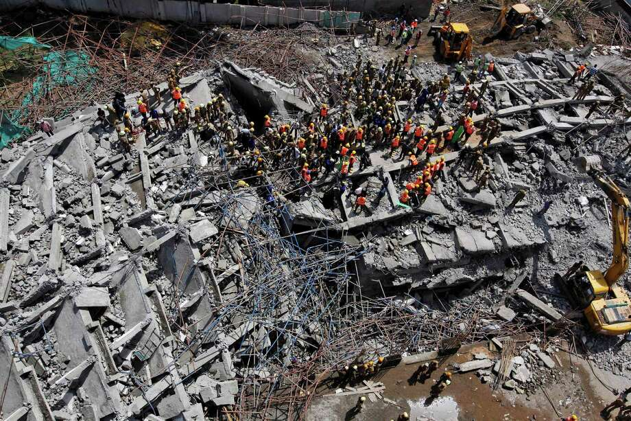 Rescuers, search for workers believed buried in the rubble of a building that collapsed late Saturday during monsoon rains on the outskirts of Chennai, India, Sunday, June 29, 2014. Police said dozens of workers have been pulled out so far and the search is continuing. Photo: Arun Sankar K, AP  / AP