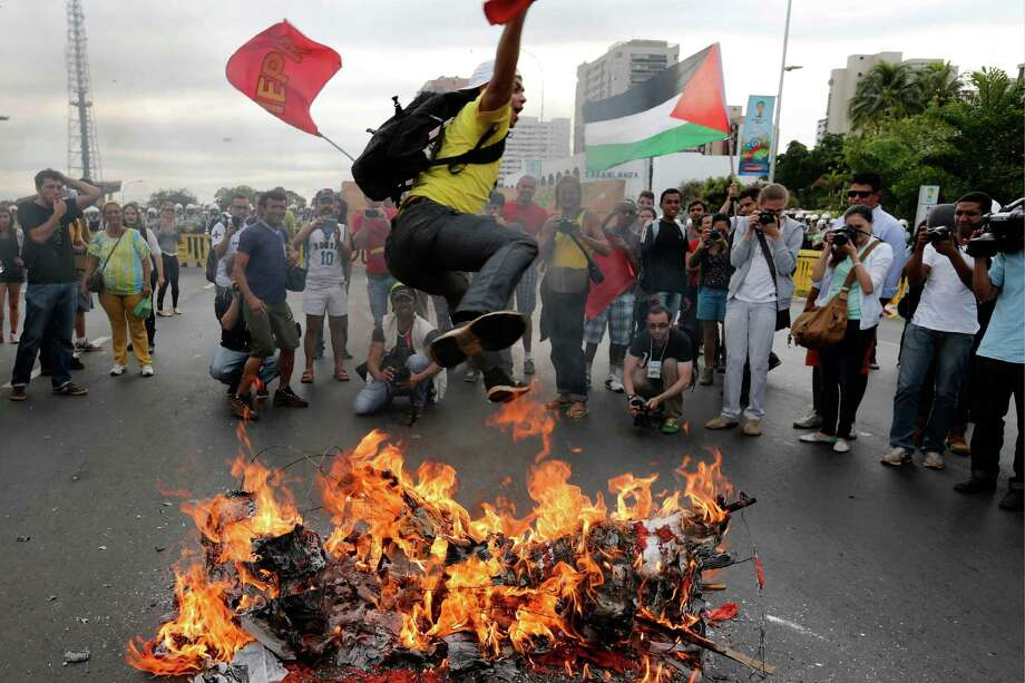 A demonstrator jumps over a fire during a protest against the World Cup soccer tournament in Brasilia, Brazil, Monday, June 23, 2014. Protesters are unhappy about the money spent on the tournament, which they believe would have been better spent on Improving the country's basic services. Photo: Eraldo Peres, AP  / AP