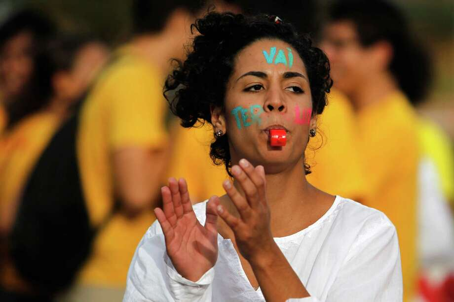 "A demonstrator, with the words ""Go Fight"" written on her face, blows on a whistle during a protest against the World Cup soccer tournament in Brasilia, Brazil, Monday, June 23, 2014. Protesters are unhappy about the money spent on the tournament, which they believe would have been better spent on Improving the country's basic services. Photo: Eraldo Peres, AP  / AP"