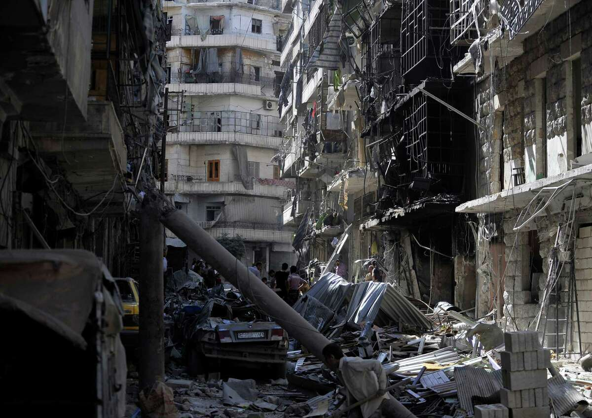 Syrians inspect the destroyed buildings following a Syrian government air strike in Aleppo, Syria, on June 26, 2014. At least 17 people including women and children were killed during an air strike by the Syrian army on opposition-held areas in Aleppo Thursday, opposition activists said. (Photo by Salih Mahmud Leyla/Anadolu Agency/Getty Images)