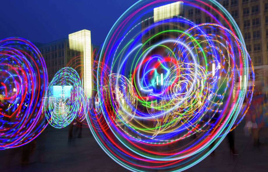 In this picture taken with the slow shutter speed of one second, hoopers perform with illuminated hula hoops during a flash mob at Alexanderplatz in Berlin, Germany, Friday, June 27, 2014. The performance was part of the Hula Hoop Festival Hoopurbia 2014, which takes place in Berlin until Sunday, June 29. Hoopurbia 2014 is the third edition of an urban Hula Hoop Festival bringing together hoopers from around the globe for six days of workshops, dance parties and performance showcases with hula hoops. Photo: Gero Breloer, AP  / AP