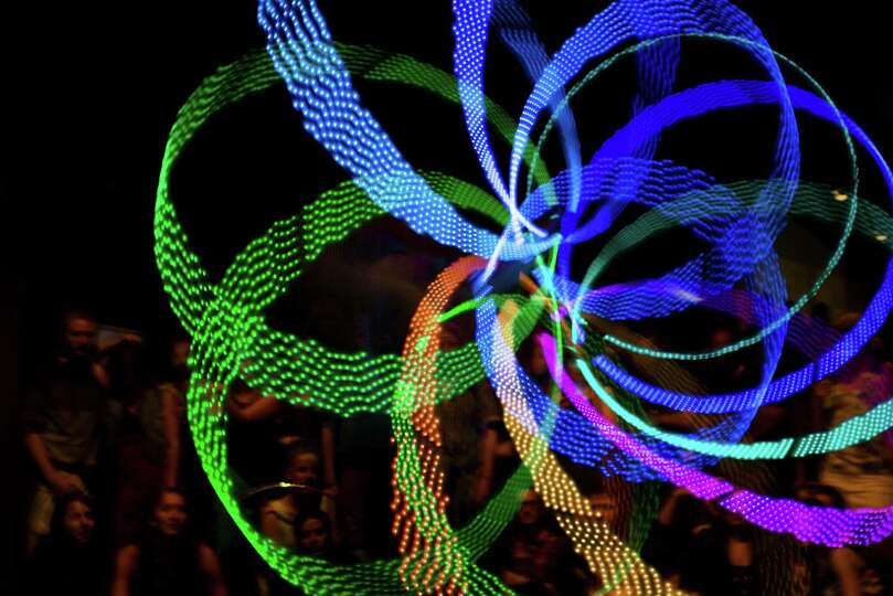 A hooper performs with illuminated hula hoops at the Hula Hoop Festival Hoopurbia 2014 in Berlin, Ge
