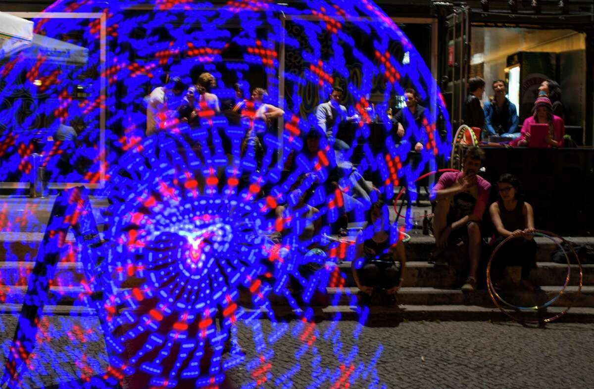 People watch a hooper warming up with an illuminated hula hoop at the Hula Hoop Festival Hoopurbia 2014 in Berlin, Germany, Sunday, June 29, 2014. Hoopurbia 2014 is the third edition of an urban hula hoop festival bringing together hoopers from around the globe for six days of workshops, dance parties and performance showcases with hula hoops.