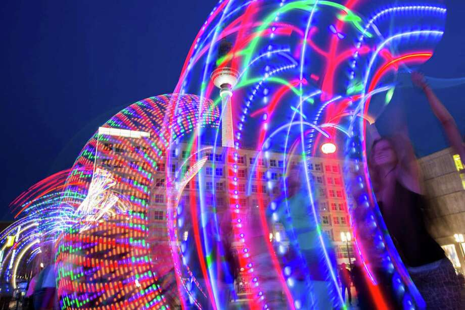 In this picture taken with the slow shutter speed of one second, hoopers perform with illuminated hula hoops during a flash mob at Alexanderplatz in Berlin, Germany, Friday, June 27, 2014. The performance was part of the Hula Hoop Festival Hoopurbia 2014, which takes place in Berlin until Sunday, June 29. Hoopurbia 2014 is the third edition of an urban Hula Hoop Festival bringing together hoopers from around the globe for six days of workshops, dance parties and performance showcases with hula hoops. Photo: Gero Breloer, AP  / AP2014