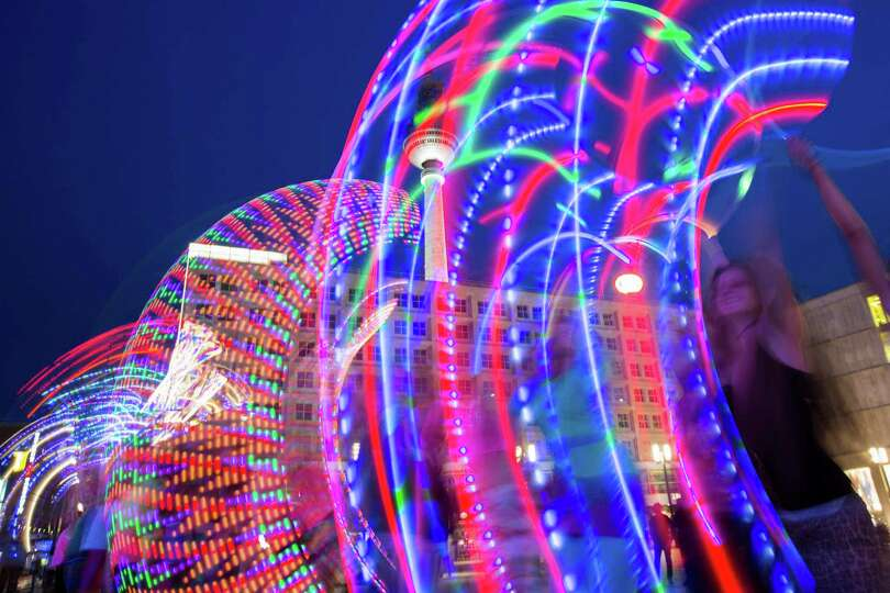 In this picture taken with the slow shutter speed of one second, hoopers perform with illuminated hu