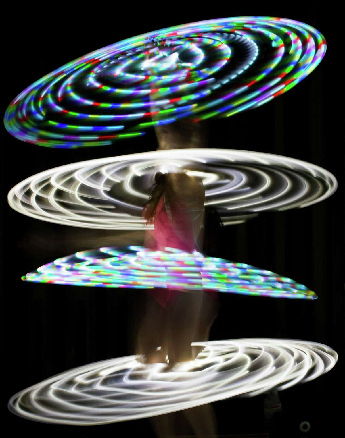 Canadian hooper Rebecca Halls performs with illuminated hula hoops at the Hula Hoop Festival Hoopurbia 2014 in Berlin, Germany, Sunday, June 29, 2014. Hoopurbia 2014 is the third edition of an urban hula hoop festival bringing together hoopers from around the globe for six days of workshops, dance parties and performance showcases with hula hoops.