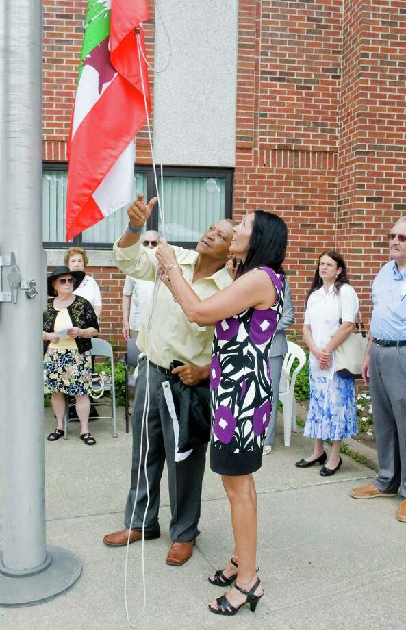Barnes Kerzent, Custodian of Public Buildings, helps Lori Kaback, Town Clerk, raise the Lebanese flag at the 11th Annual Lebanon American Day Recognition Ceremony held at City Hall. Sunday, June 29, 2014 Photo: Scott Mullin / The News-Times Freelance