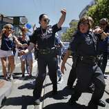 Two police officers dance together during the SF Pride Parade along Market Street on June 29, 2014 in San Francisco, CA.