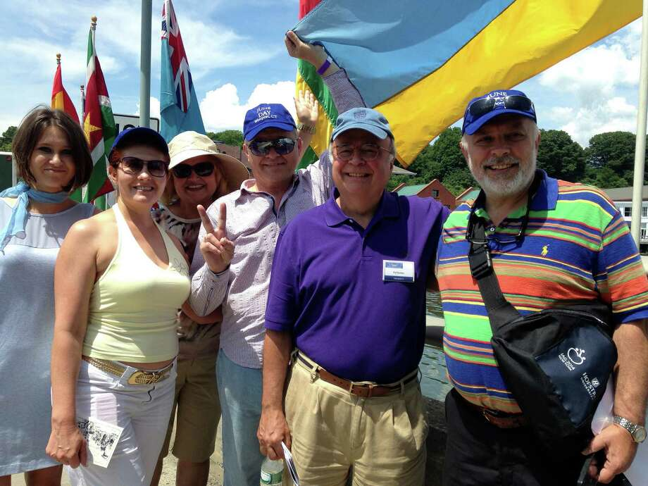 Edward Gerber, president of the Westport Historical Society, led a group of Ukrainian visitors from the United Nations on a walking tour downtown during Saturday's jUNe Day program. Here, they pause for a photo beneath Ukraine's flag on the Ruth Steinkraus Cohen bridge over the Saugatuck River. Photo: Contributed Photo / Westport News