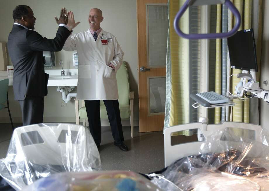 Top Kaiser executive Claude Watts Jr. (left) and Dr. John Loftus, physician in chief, high-five at the new center. Photo: Paul Chinn, The Chronicle