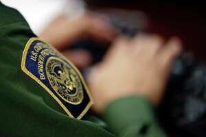 In this June 5, 2014 picture, a Border Patrol agent uses a headset and computer to conduct a long distance interview by video with a person arrested crossing the border in Texas, from a facility in San Diego. Hit with a dramatic increase of Central Americans crossing in South Texas, the Border Patrol is relieving staffing woes by enlisting agents in less busy sectors to process arrests through video interviews.  (AP Photo/Gregory Bull)