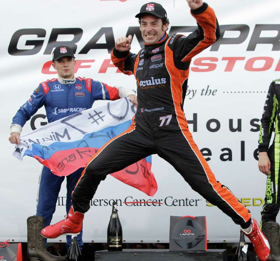 IndyCar driver Simon Pagenaud jumps on the trophy stage celebrating his first place win of the IndyCar Series Race #2 at the Grand Prix of Houston at NRG Park Sunday, June 29, 2014, in Houston. Teammate and second place finisher Mikhail Aleshin is shown left. Photo: Melissa Phillip, Houston Chronicle / © 2014  Houston Chronicle