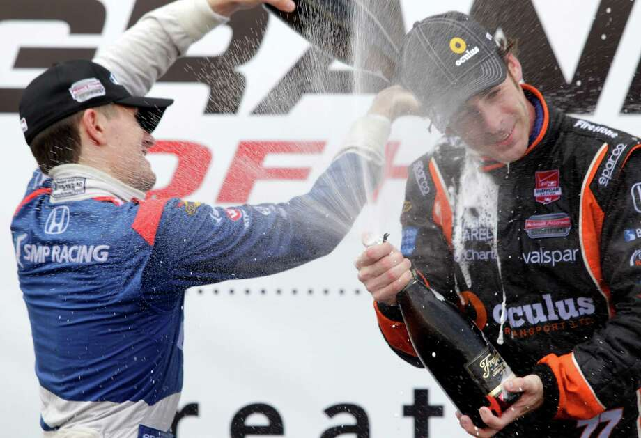 IndyCar driver Mikhail Aleshin, left, second place finisher, and Simon Pagenaud, right, first place finisher, spray champagne during trophy ceremony at the IndyCar Series Race #2 at the Grand Prix of Houston at NRG Park Sunday, June 29, 2014, in Houston. Photo: Melissa Phillip, Houston Chronicle / © 2014  Houston Chronicle