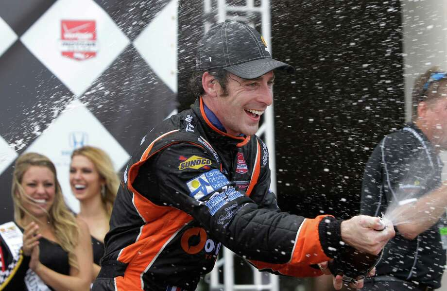 IndyCar driver Simon Pagenaud, first place finisher, sprays champagne during trophy ceremony at the IndyCar Series Race #2 at the Grand Prix of Houston at NRG Park Sunday, June 29, 2014, in Houston. Photo: Melissa Phillip, Houston Chronicle / © 2014  Houston Chronicle