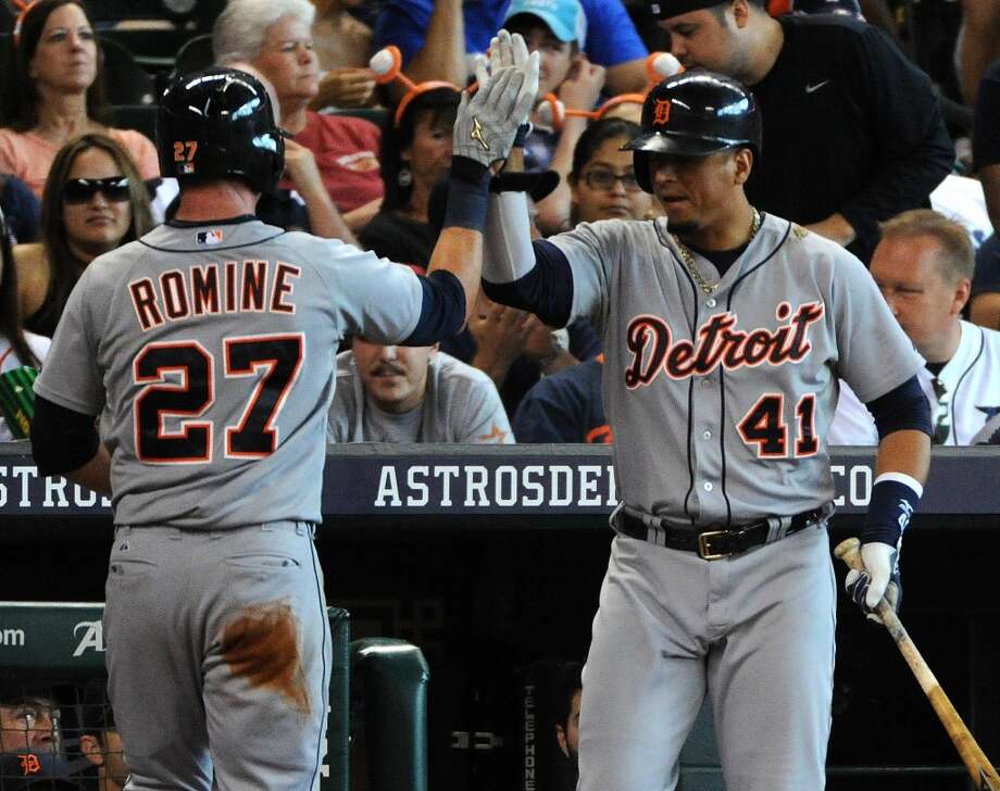 Tigers second baseman Andrew Romine (27) celebrates scoring the Tigers' first run of the game with designated hitter Victor Martinez. Photo: Eric Christian Smith, For The Chronicle