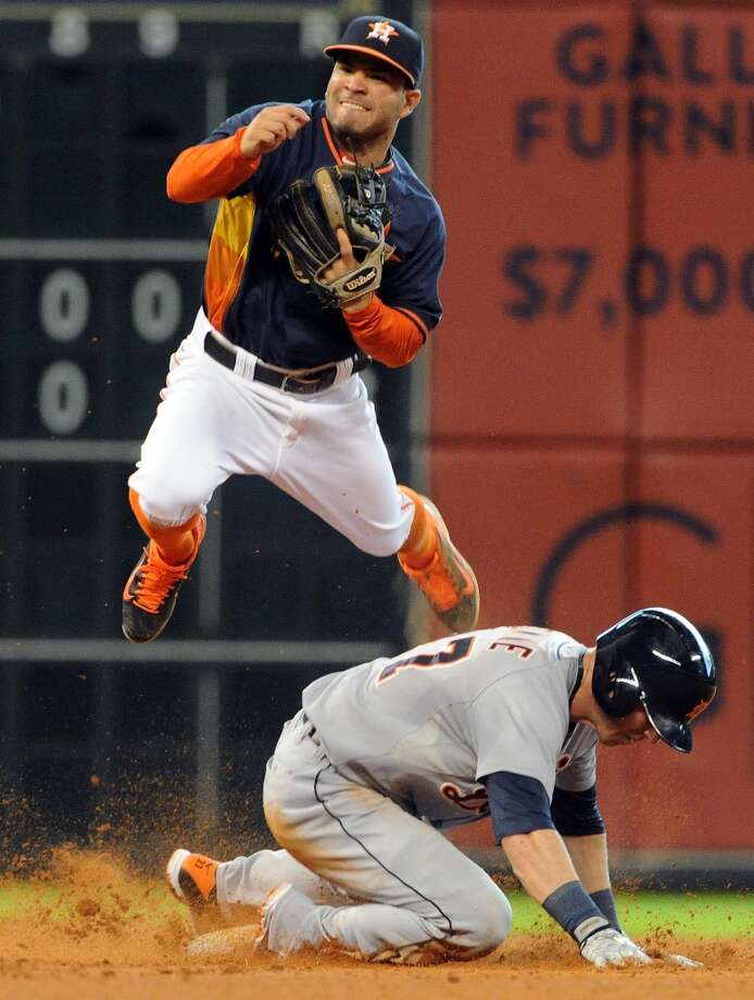 Astros second baseman Jose Altuve, top, leaps over Tigers second baseman Andrew Romine after forcing Romine out in a double play. Photo: Eric Christian Smith, For The Chronicle