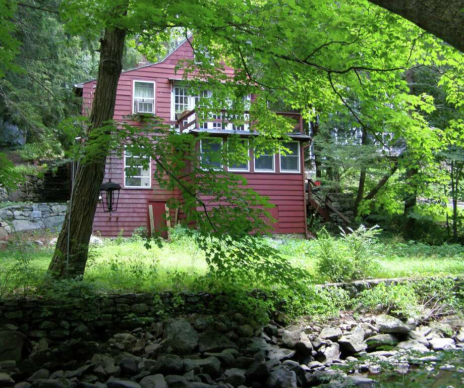 The red house alongside the Aspetuck River at 497 Westport Turnpike is on the market for $399,900. Photo: Contributed Photo / Fairfield Citizen