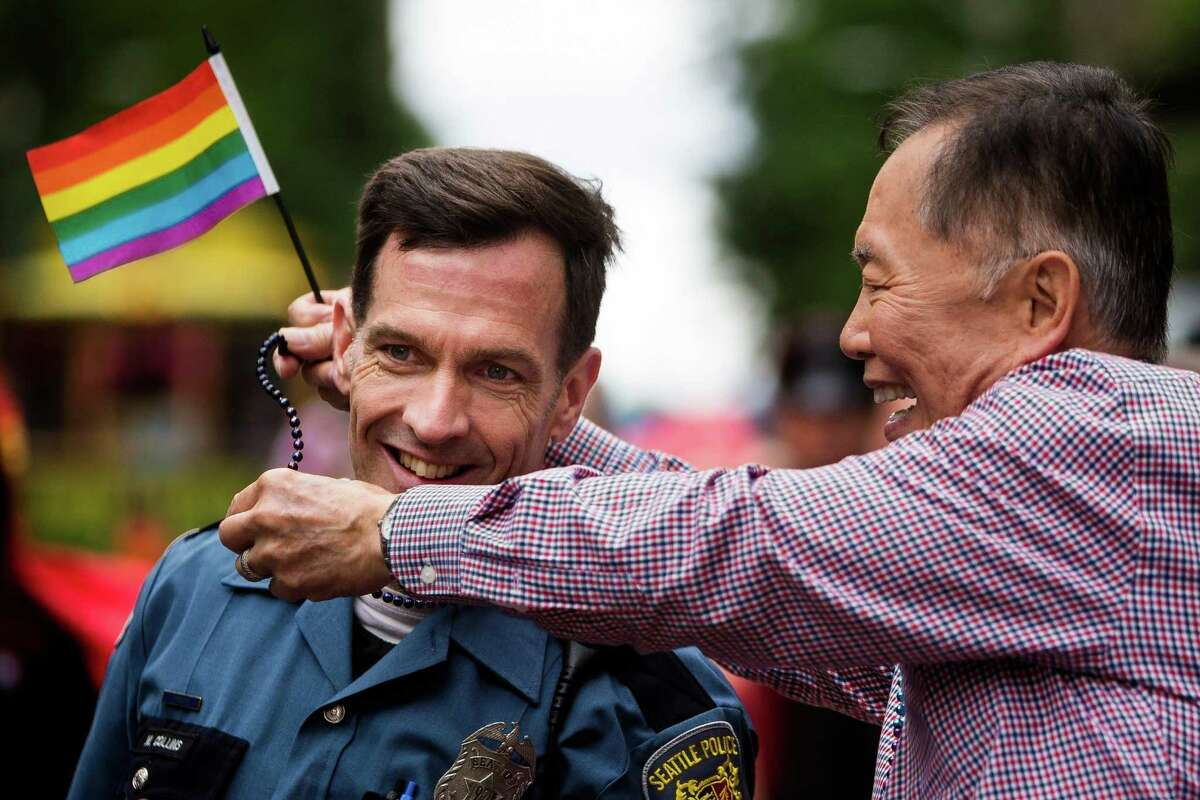 George Takei, right, of Star Trek fame and acting Grand Marshall of the 40th annual Seattle Pride Parade, drapes beads over a Seattle Police Department officer Sunday, June 29, 2014, in Seattle, Wash. This year's theme was