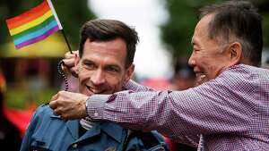 """George Takei, right, of Star Trek fame and acting Grand Marshall of the 40th annual Seattle Pride Parade, drapes beads over a Seattle Police Department officer Sunday, June 29, 2014, in Seattle, Wash. This year's theme was ÒGenerations of Pride."""""""