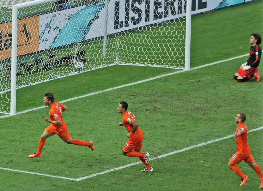 The Netherlands' Klaas-Jan Huntelaar, left, trailed by two teammates, celebrates after converting a penalty kick in injury time to win. Photo: Themba Hadebe, STF / AP
